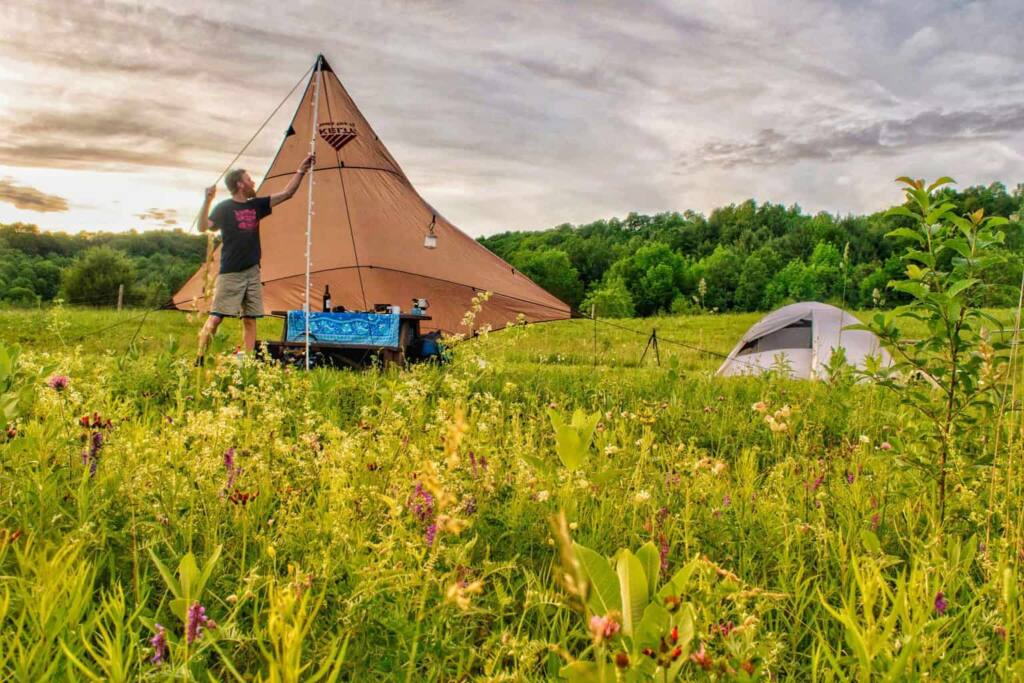 A man sets up a tarp over a picnic table at a campsite.