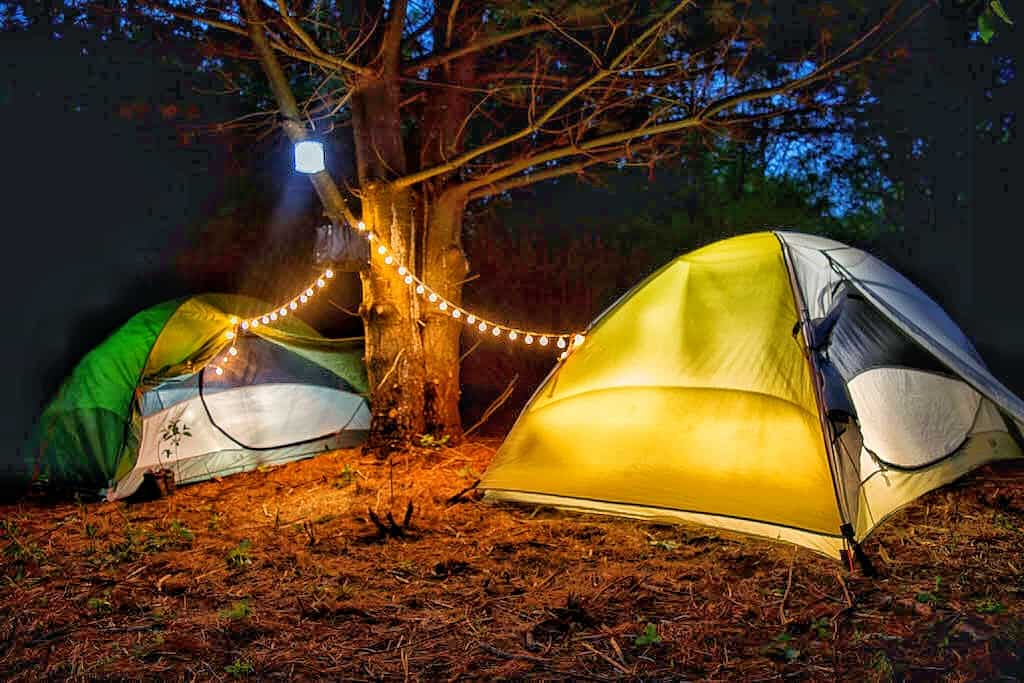 Two tents glowing in the night.
