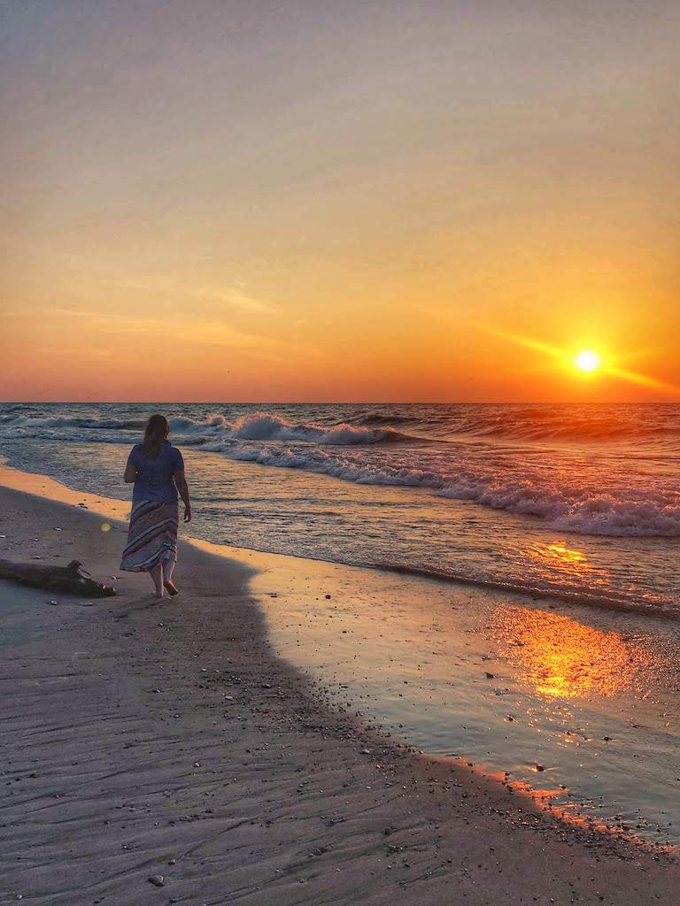 A woman walks along the shore at Indiana Dunes National Park at sunset.