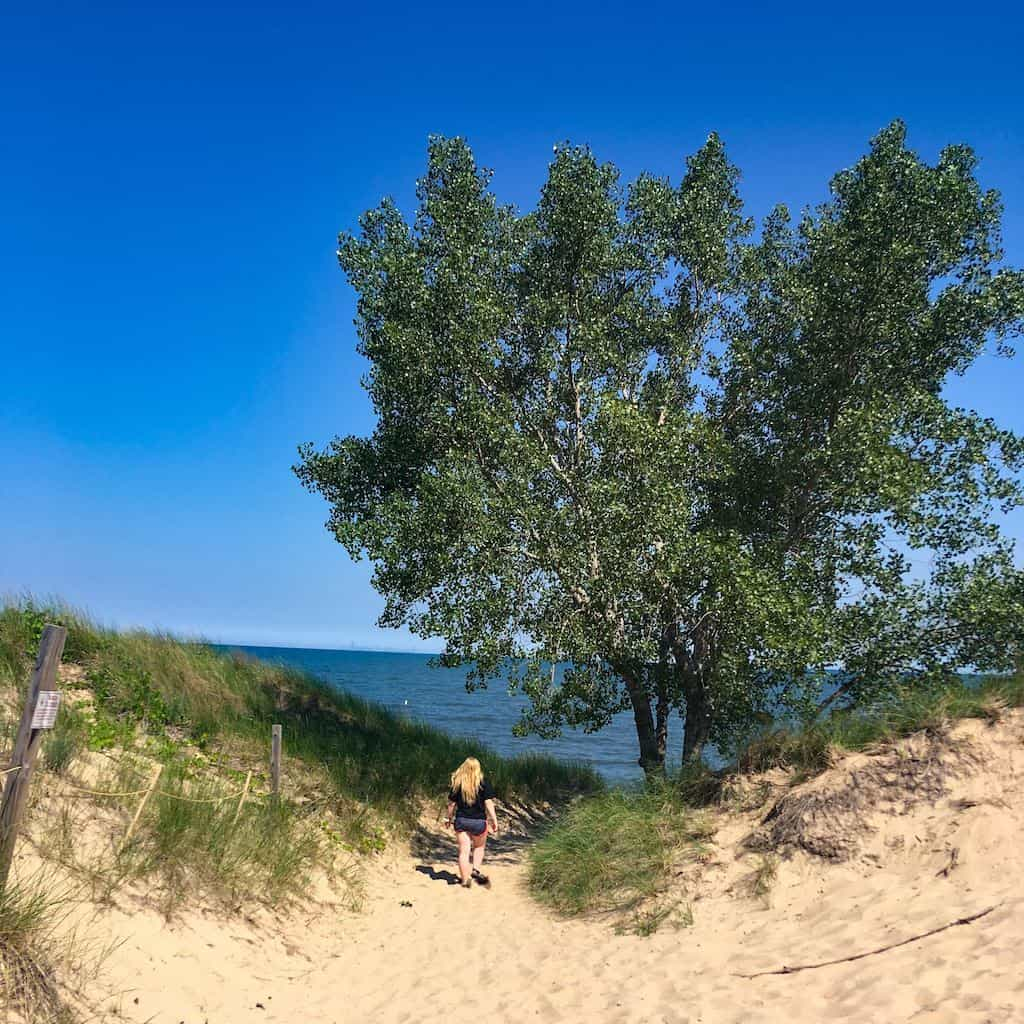 A woman walks down a trail to West Beach at Indiana Dunes National Park.