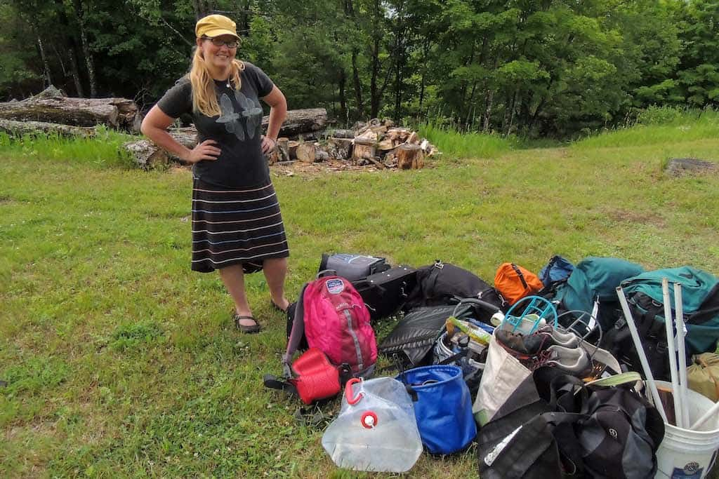 A woman stands outside next to a pile of outdoor gear.