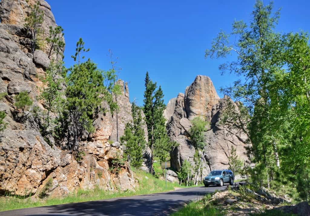 A car drives on the Needles Highway in Custer State Park, South Dakota