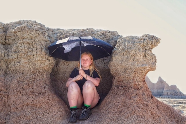 A girl sits on a rock formation in Badlands National Park. She is holding an umbrella to protect herself from the harsh sun.
