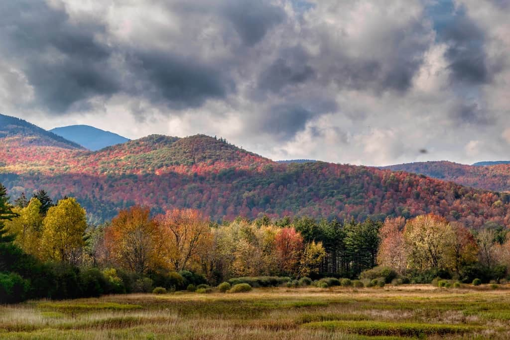 A moutainous field in the Adirondacks during fall foliage season.
