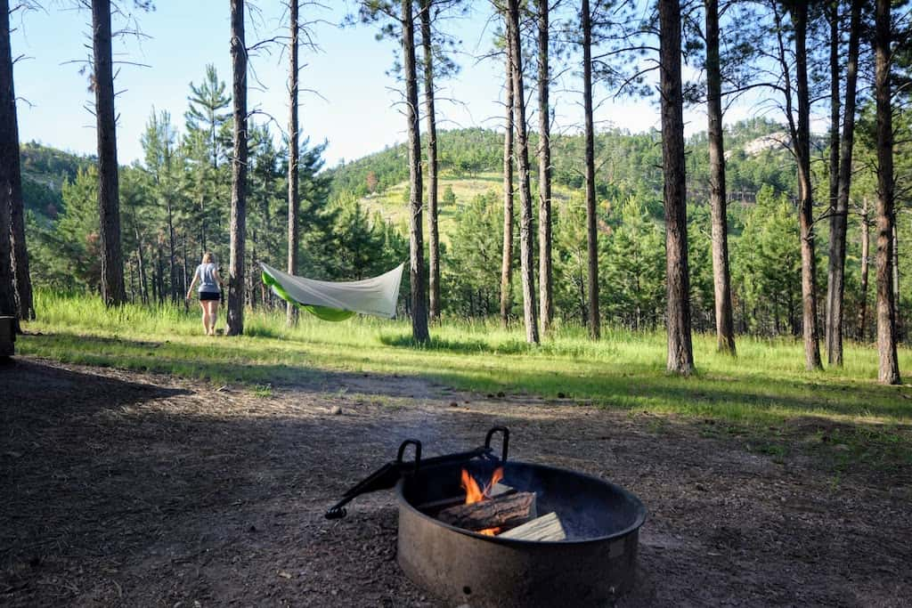 A firepit burning in Blue Bell Campground Custer State Park with a hammock in the distance.