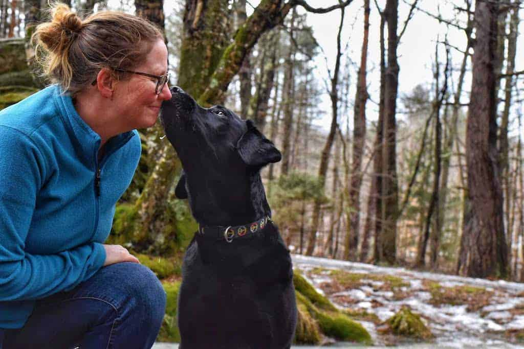 A woman sits outside next to a black lab. They are touching noses.