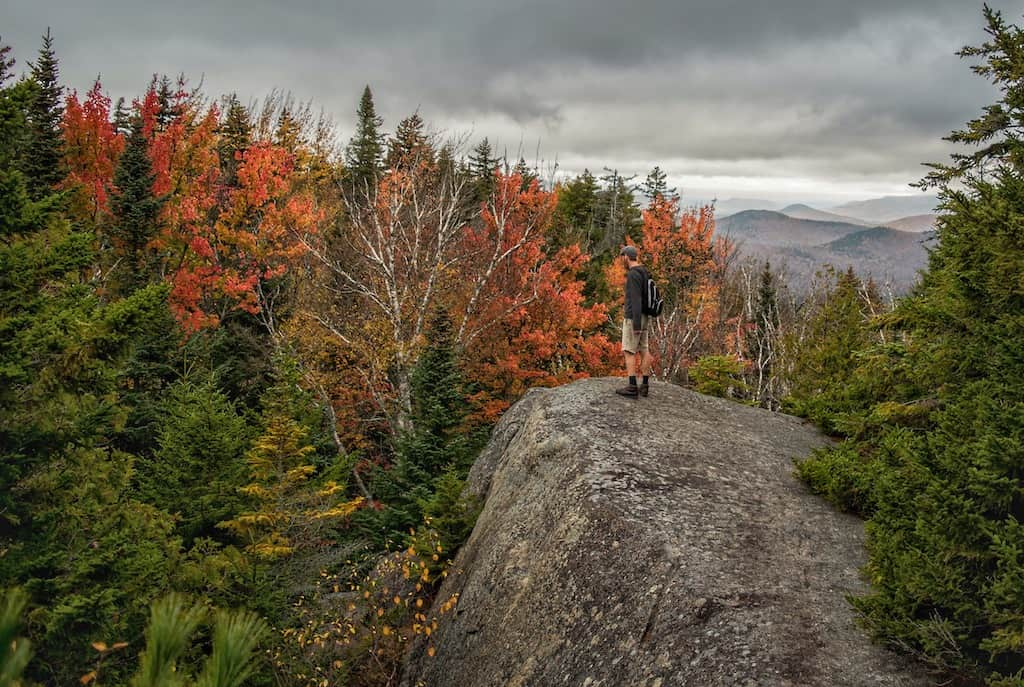 A man stands on a rock admiring the fall foliage from Mount Jo in the Adirondacks of New York.