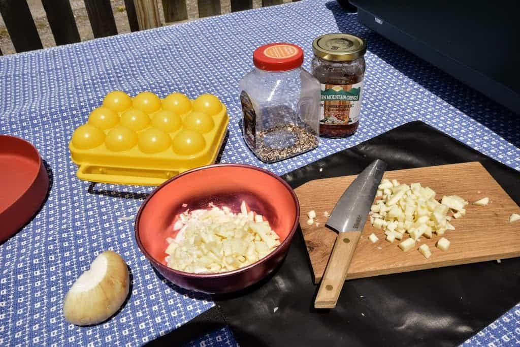a cutting board with chopped onions and a variety of ingredients on a picnic table for camping.