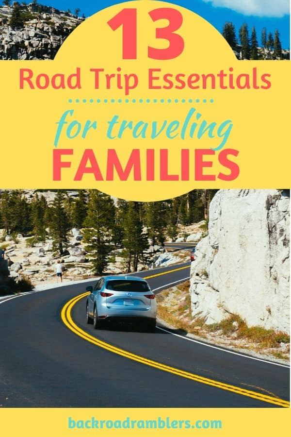 A car driving on a winding road. Caption reads: 13 Road Trip Essentials for Traveling Families.