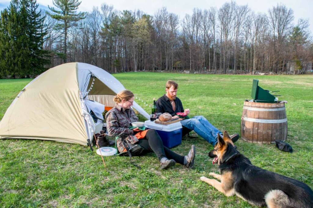 A man and a woman sit in front of a tent eating dinner while a German Shepherd watches over them on a dog-friendly camping trip.