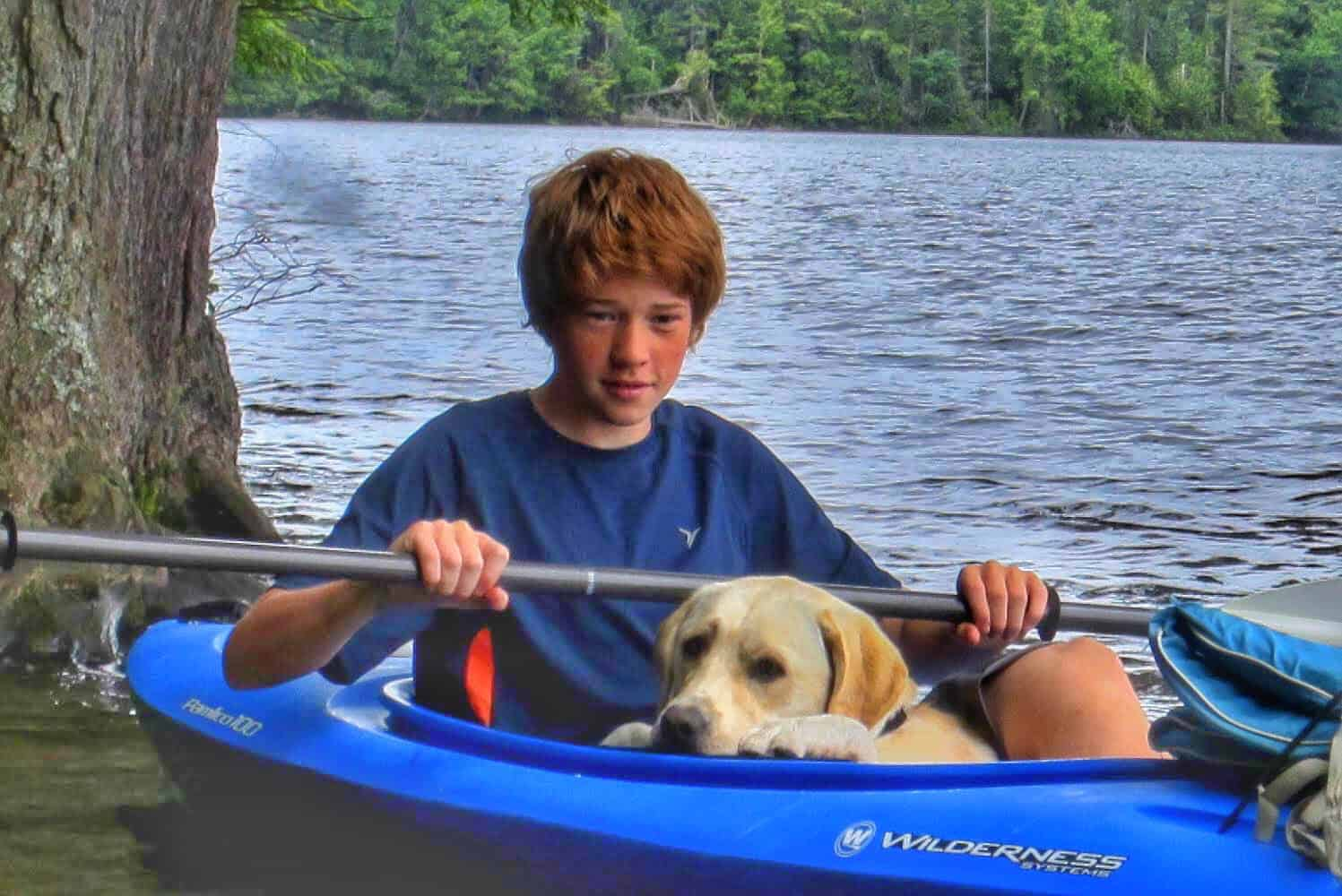 A boy and a dog in a blue kayak on a peaceful lake.