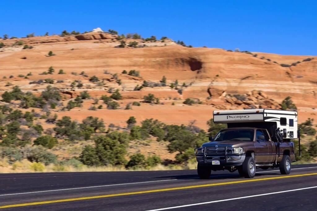 A truck camper driving through the desert