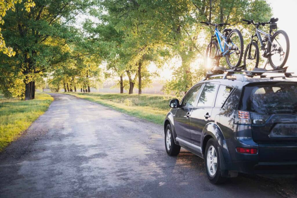 A car with bikes on a rack drives along a forest road