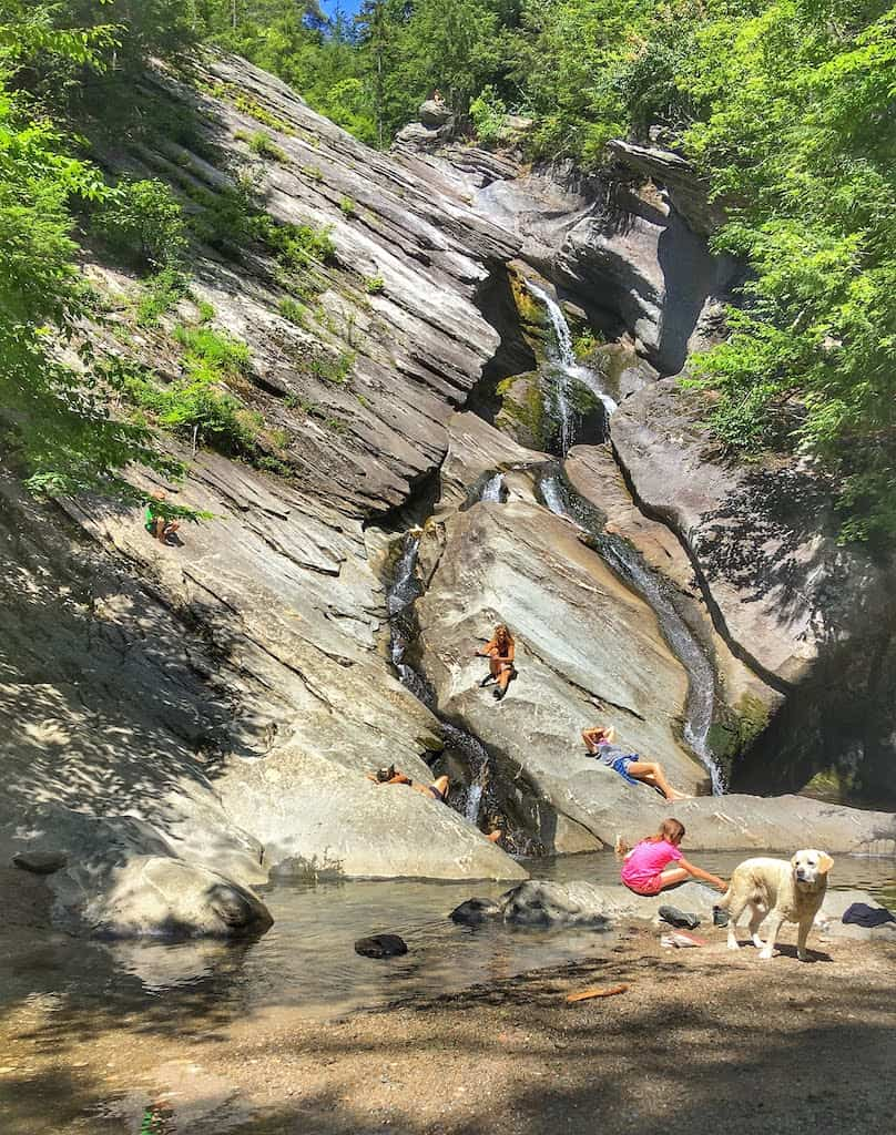 Several people lounge on the sunny rocks near Hamilton Falls in Jamaica State Park, Vermont