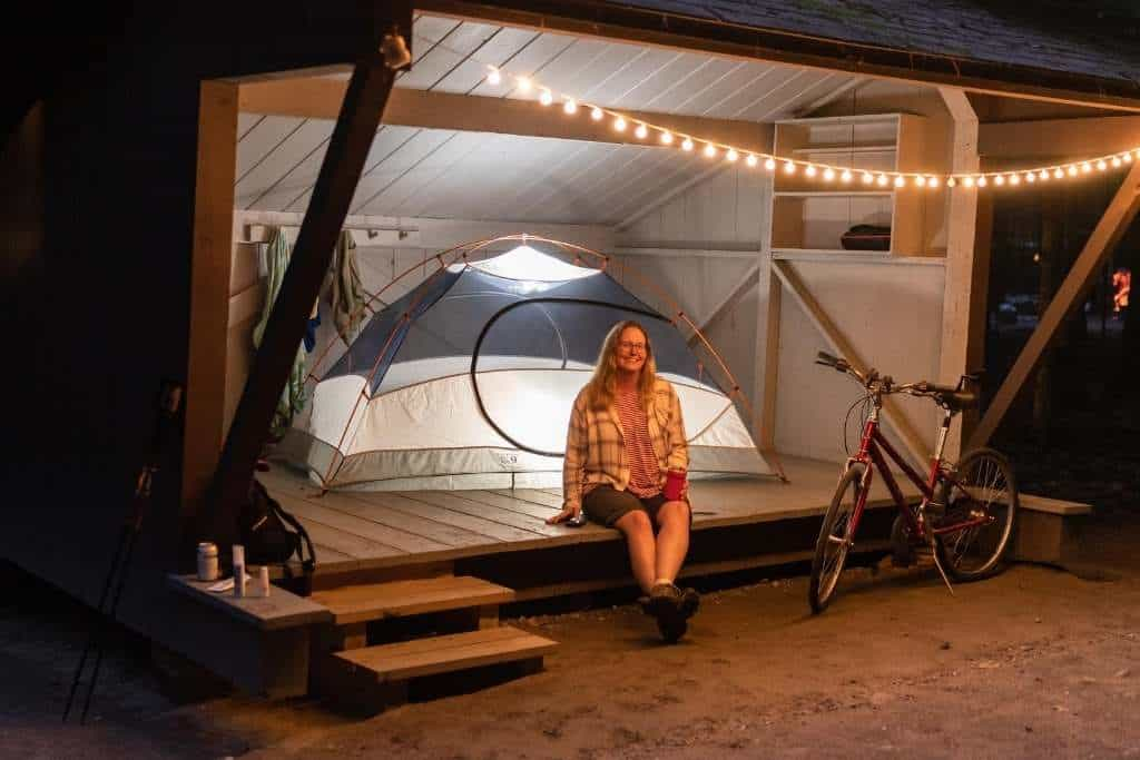 A woman sits in a lean-to next to a lit-up tent at night. There is a bike next to her and twinkly lights hanging from the ceiling. Jamaica State Park, Vermont.