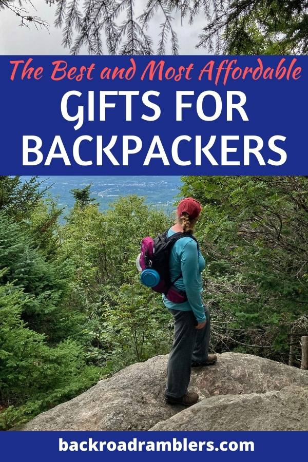 A woman stands at the top of a mountain looking out at the view. Caption reads: The best gifts for backpackers