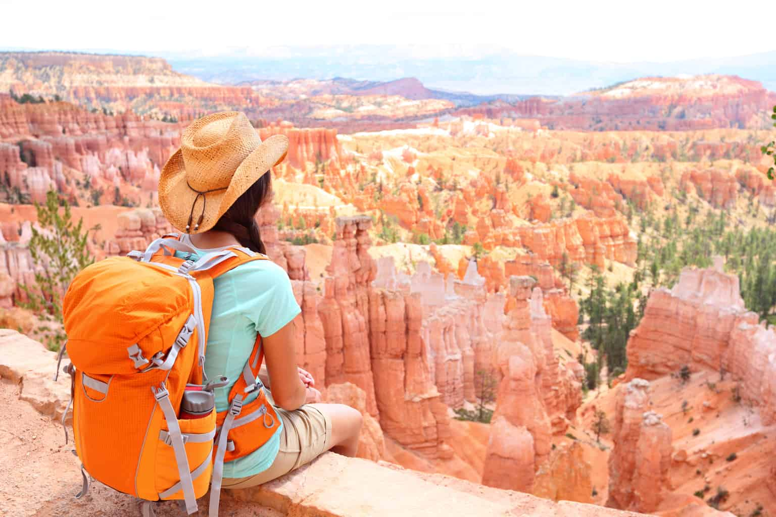 A woman sits on a ledge looking out at the view at Bryce Canyon. She is wearing an orange backpack.