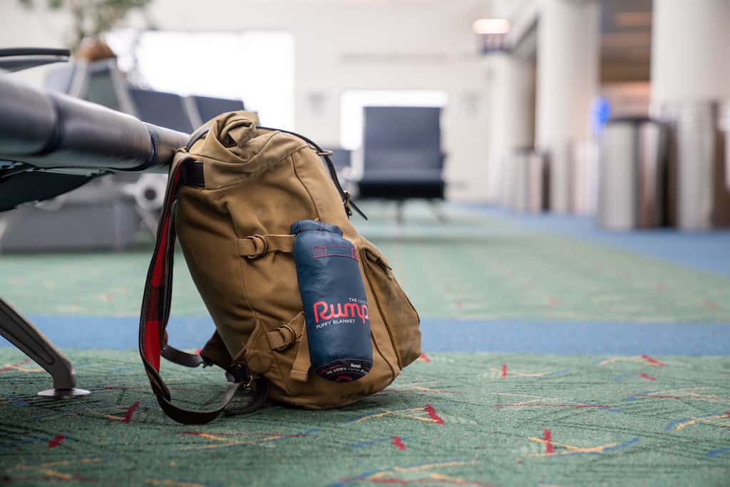 A brown backpack lying on the floor of an airport. A navy blue Rumpl blanket is attached to the outside.