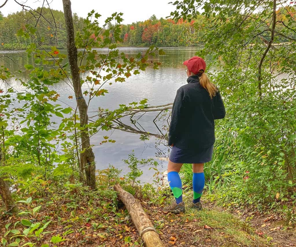 A woman stands on the shore of a lake looking out at the water. She is wearing Lily Trotters compression socks.