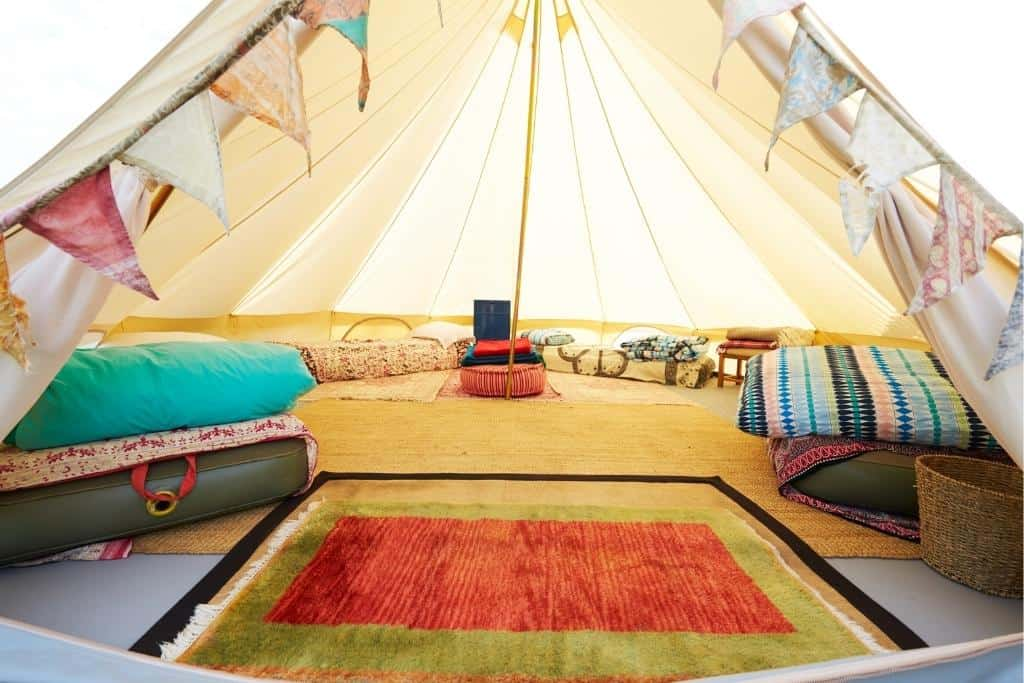 A fully decorated glamping ent with several beds, rugs, pillows, and flags inside