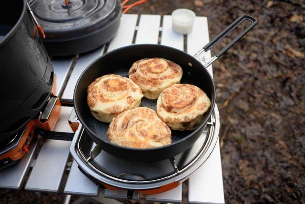 A camping table with a frying pan full of cinnamon rolls on it.