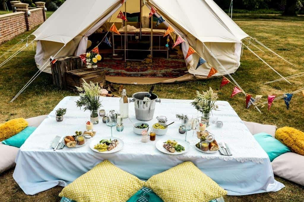 A photo showing a glamping tent with an elaborately set table in front of it.