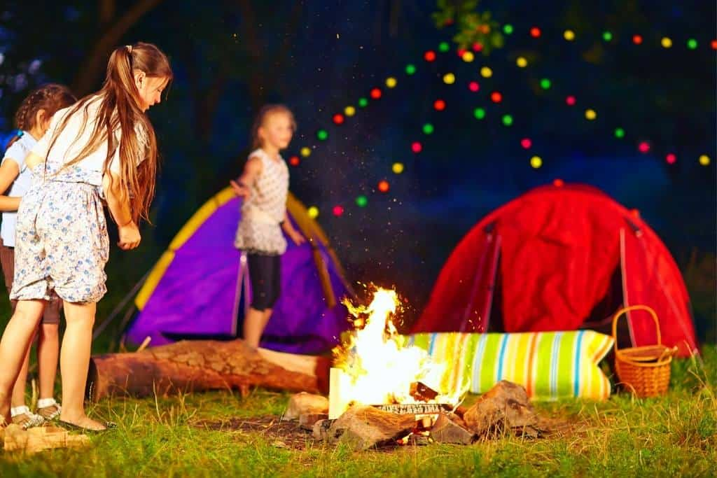several kids standing near a campfire in front of two tents.