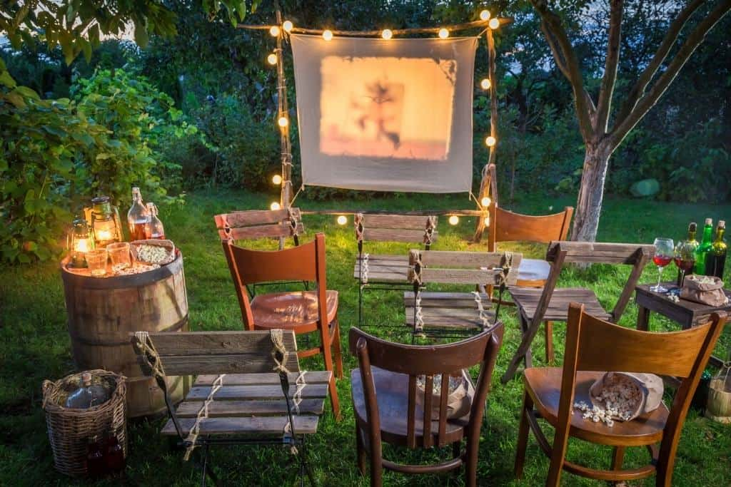 A backyard movie setup with empty chairs, candles, and twinkling lights