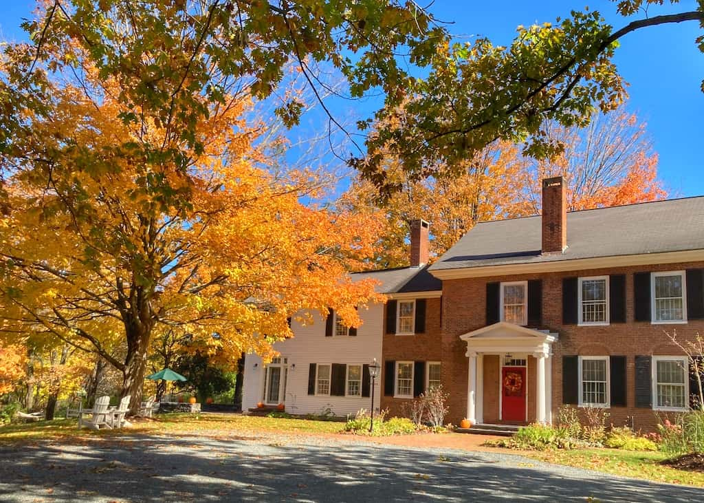 A historic home in downtown Woodstock, Vermont, surrounded by fall foliage