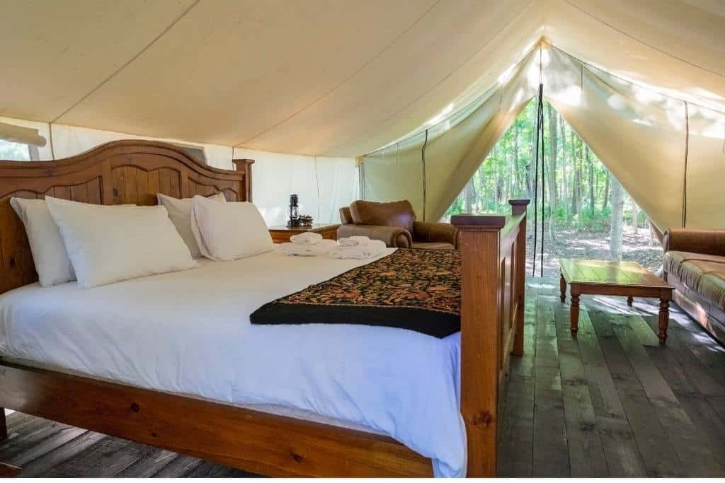 A glamping tent with a large bed in it.