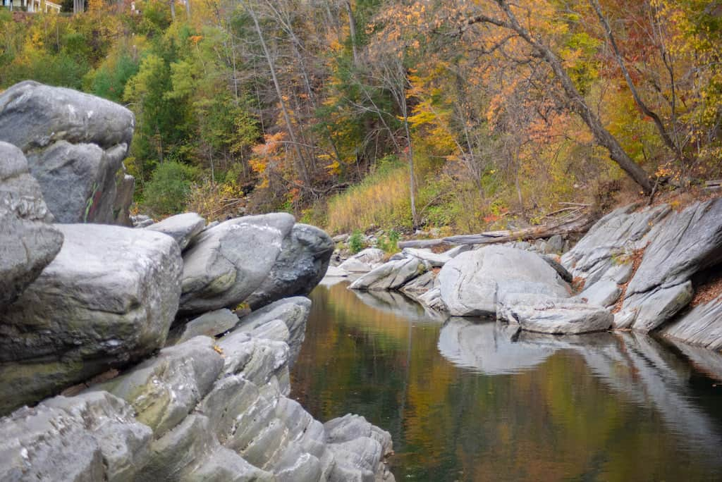Autum foliage reflected in. the Ottauquechee River at Quechee Gorge