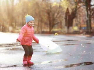 A child stands in a mud puddle wearing warm winter clothes for toddlers. She has a smile on her face.