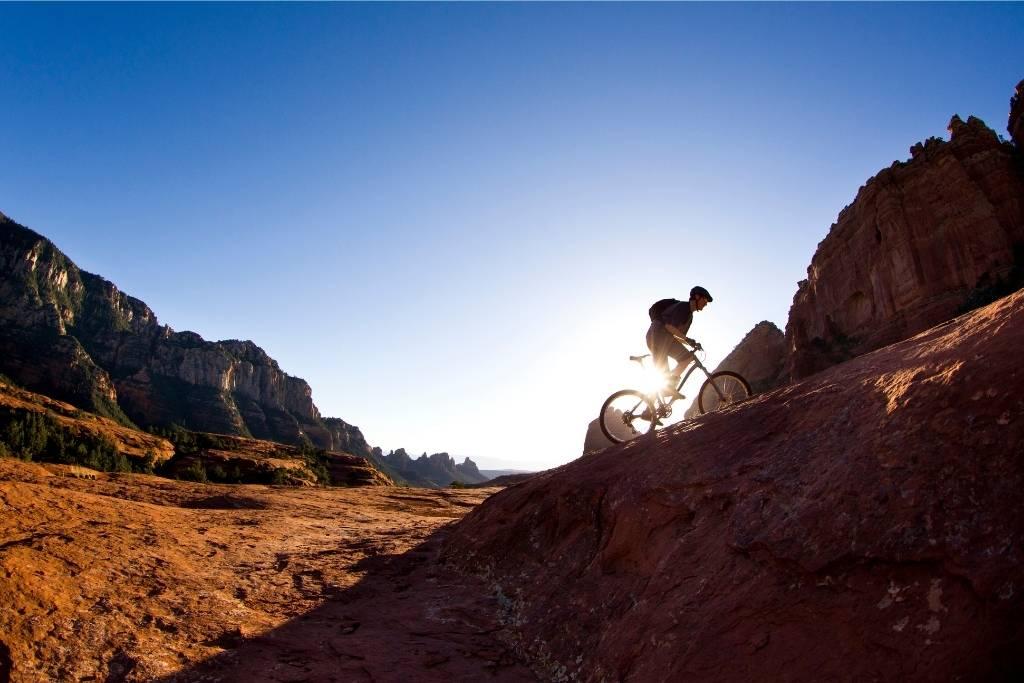 A man mountain bikes in SARA Park in Lake Havasu City, Arizona during the sunset