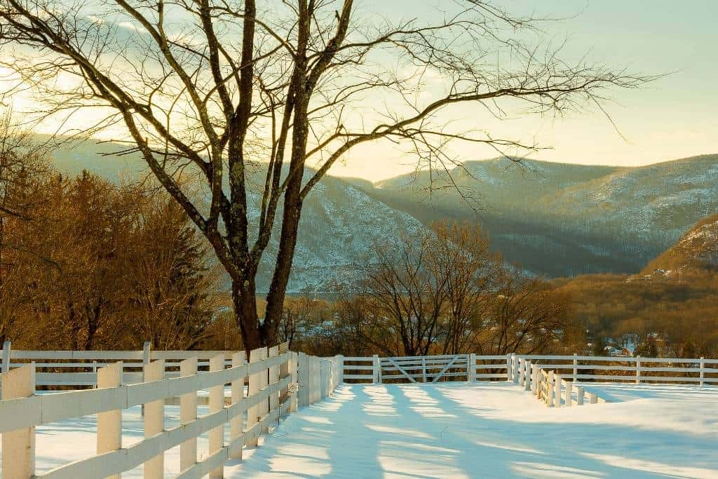 A view of a Hudson Valley, New York farm field with a white fence around it covered with snow. There are mountains in the background.