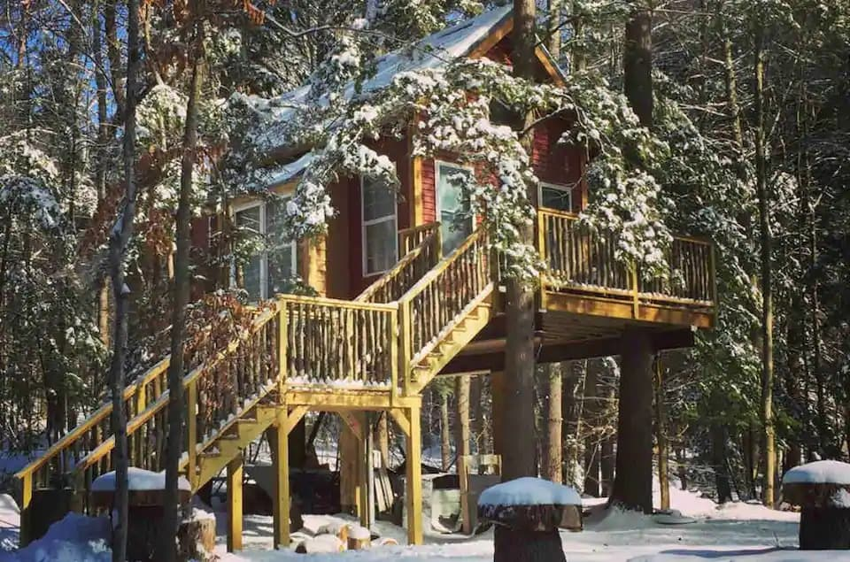 a snow-covered treehouse for rent in New Hampshire