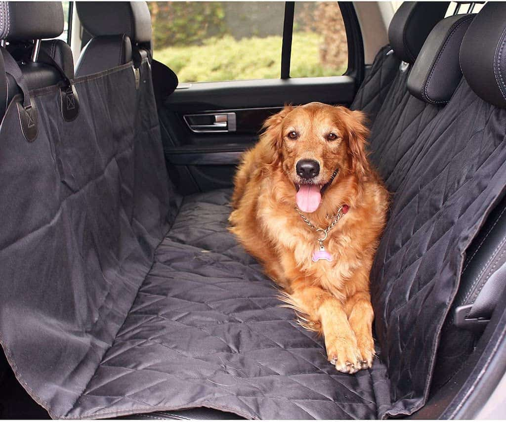 A golden retriever lies in the backseat of a car on a waterproof cover.