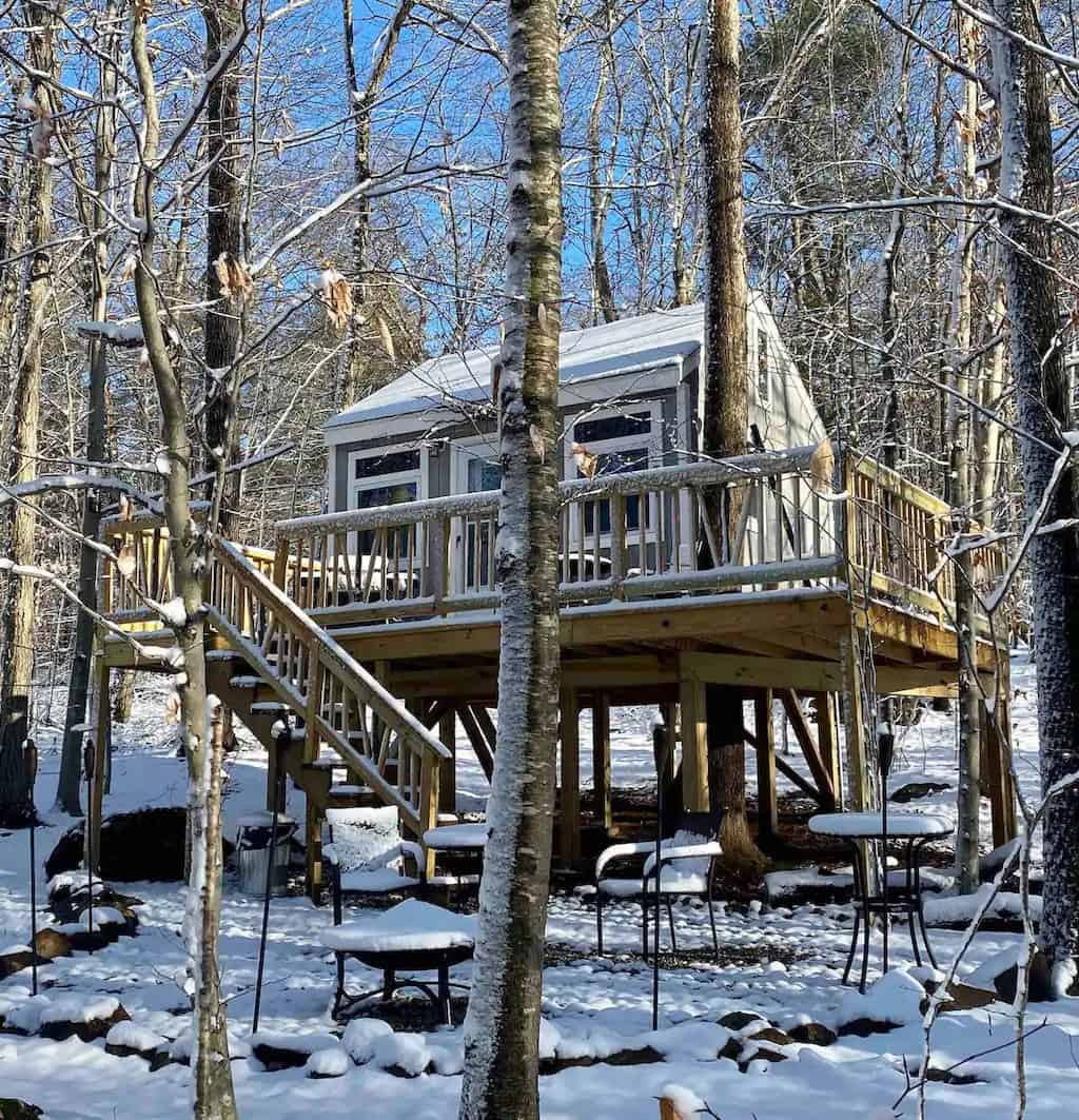 A glamping treehouse in Connecticut surrounded by snowy woods. Photo credit: Airbnb