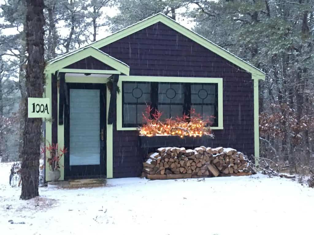 A small glamping cottage for rent in Wellfleet,MA. The cottage is in the woods and surrounded by snow. Photo credit: Airbnb