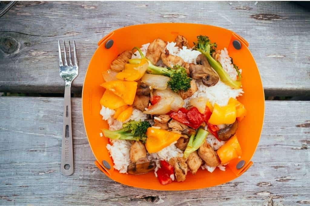 A vegetable stir-fry in an orange camping bowl on a picnic table.