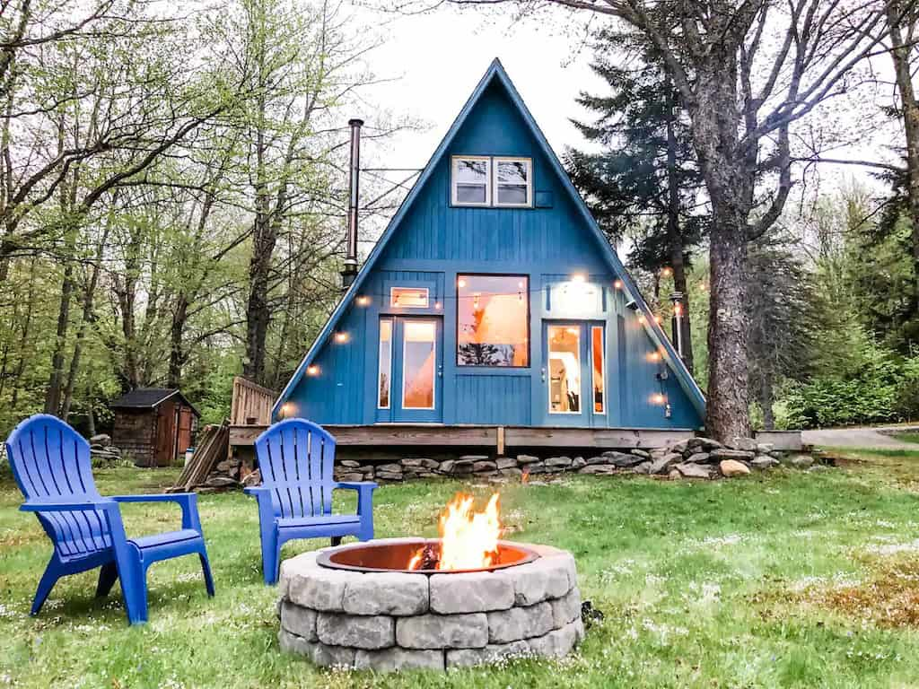 A cozy Vermont cabin painted blue with twinkly lights and a fire pit. photo source: Airbnb