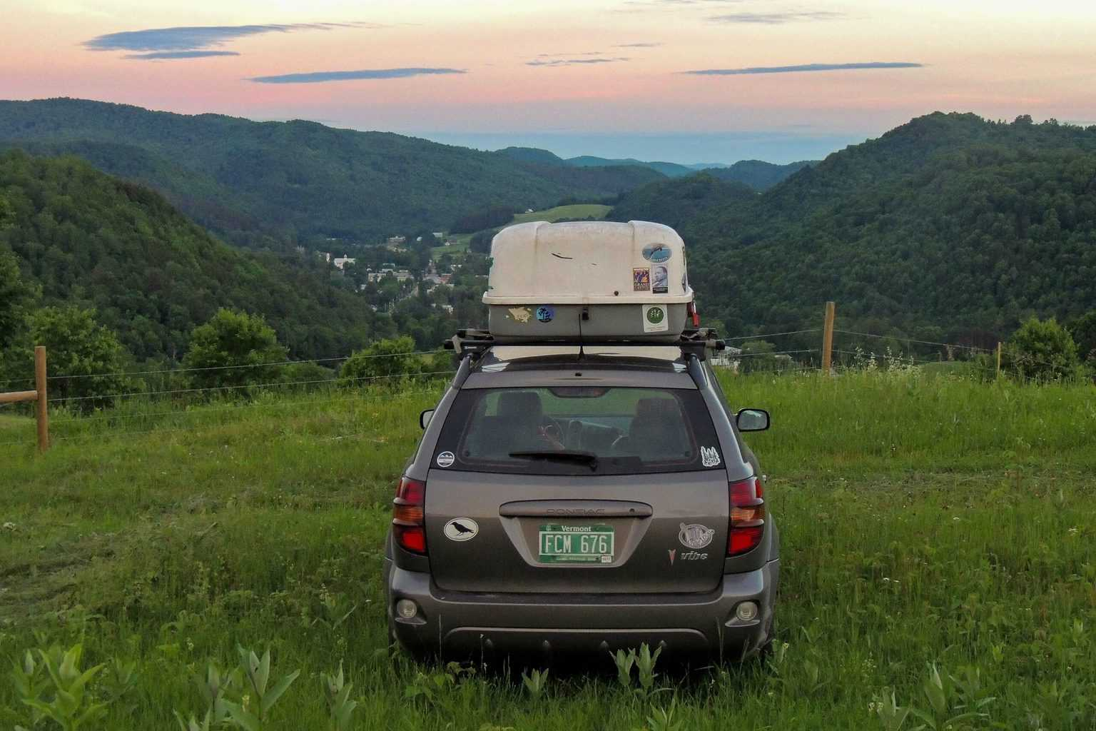The back of a grey car with a white cargo carrier on top of it pointing toward a mountain sunset.