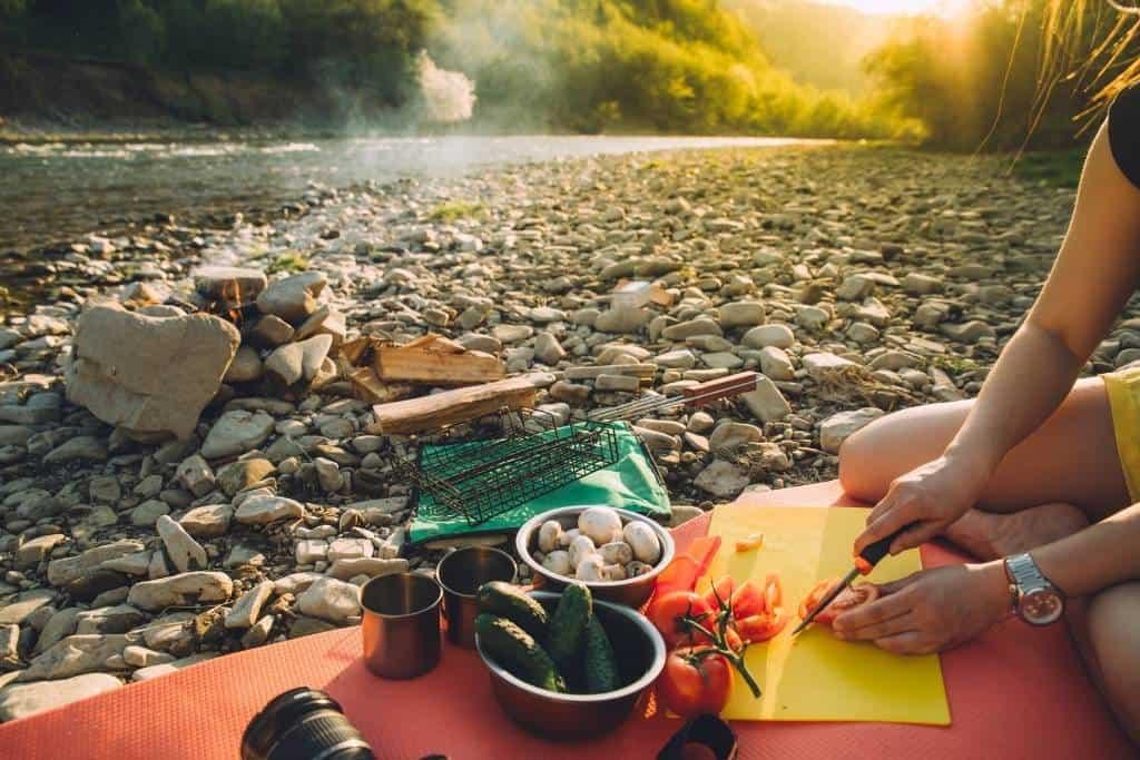 preparing food next to a river.
