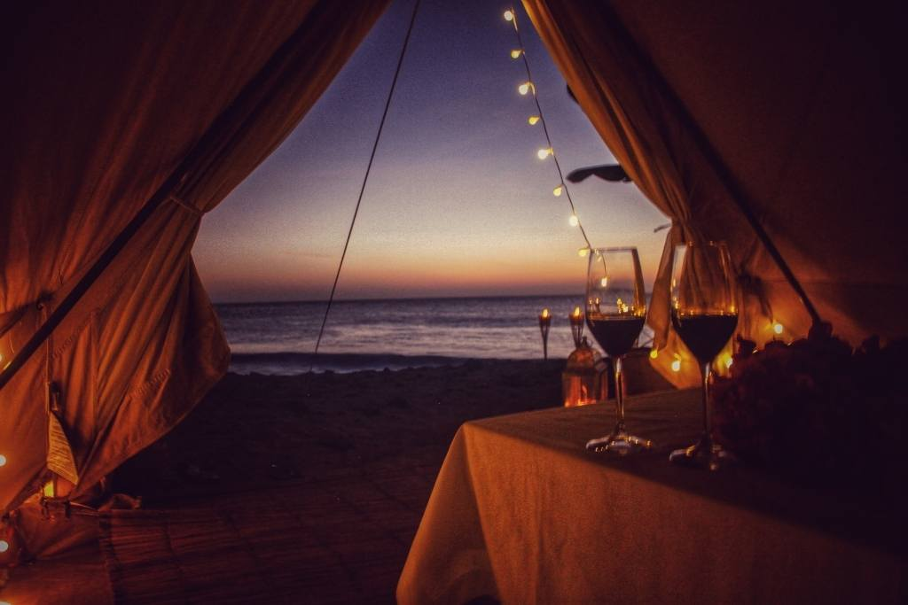 A glamping tent with two glasses of wine on a low table. You can see a view of the ocean through the tent window.