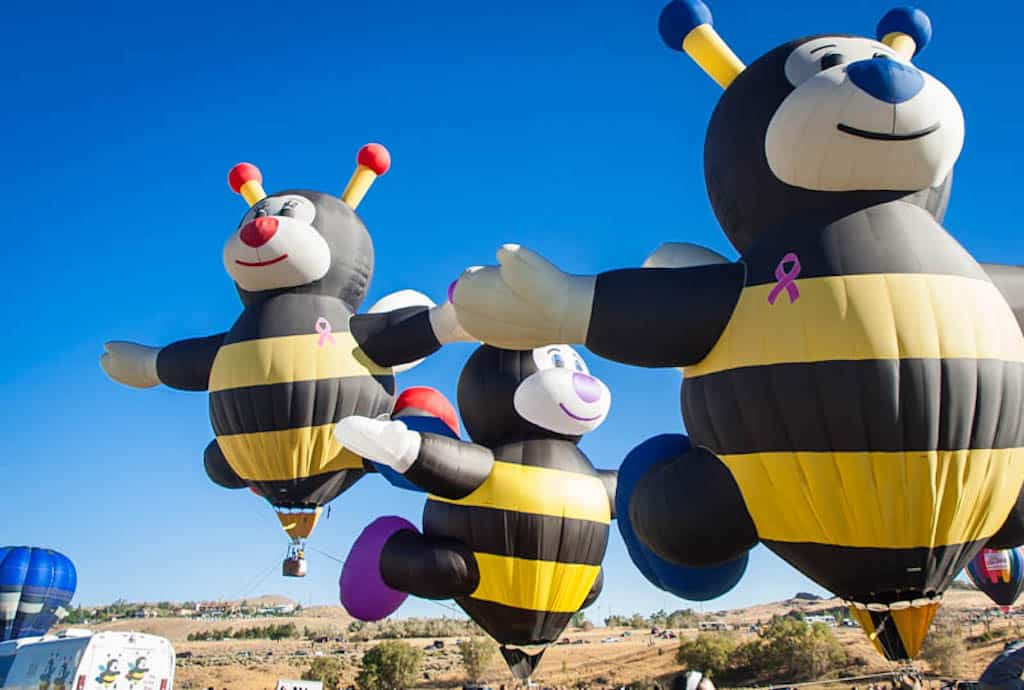 Several hot air balloons shaped like bumble bees in the sky during the Great Reno Balloon Race.