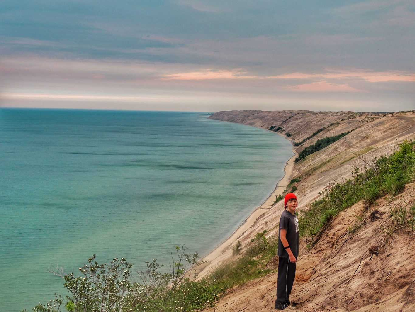 Rowan standing on a dune at the edge of Lake Superior at Pictured Rocks National Lakeshore in Michigan.