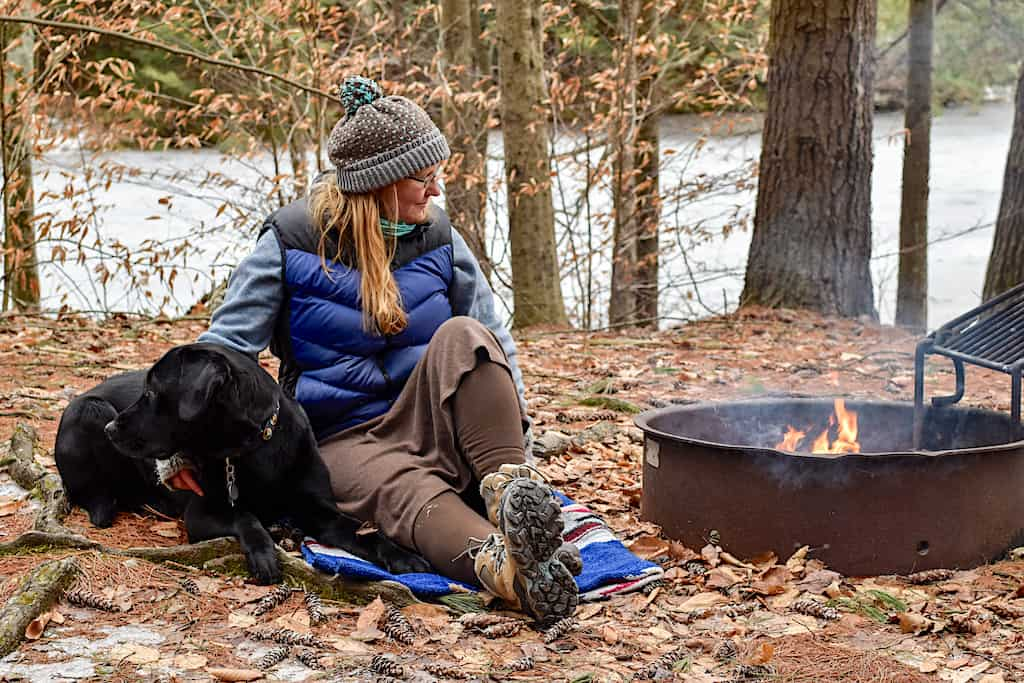 Me, sitting next to a winter campfire with my favorite black lab, Flynn.