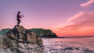 a person stands on a large rock to watch the sunset over the Bay of Fundy.