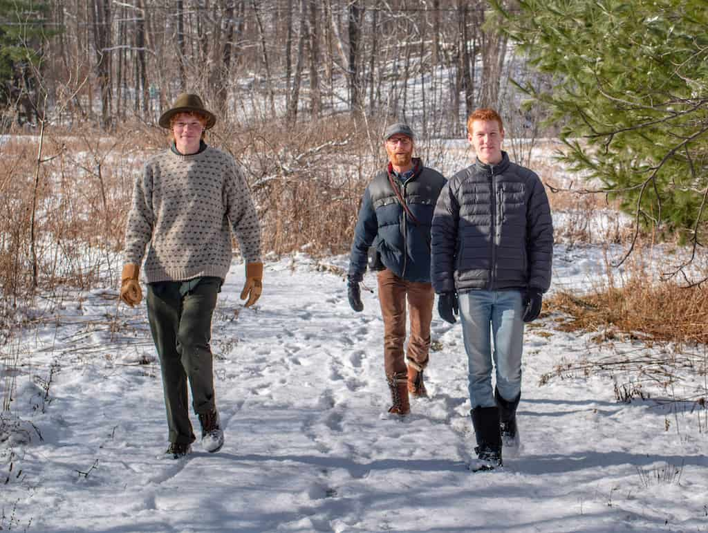 Rown, Eric, and Gabe walking through the snow on a winter day.