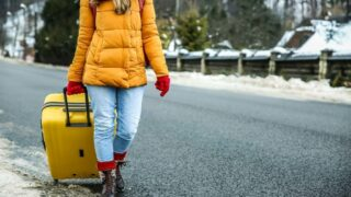 a woman in a yellow jacket pulls a yellow suitcase down the road in the winter.