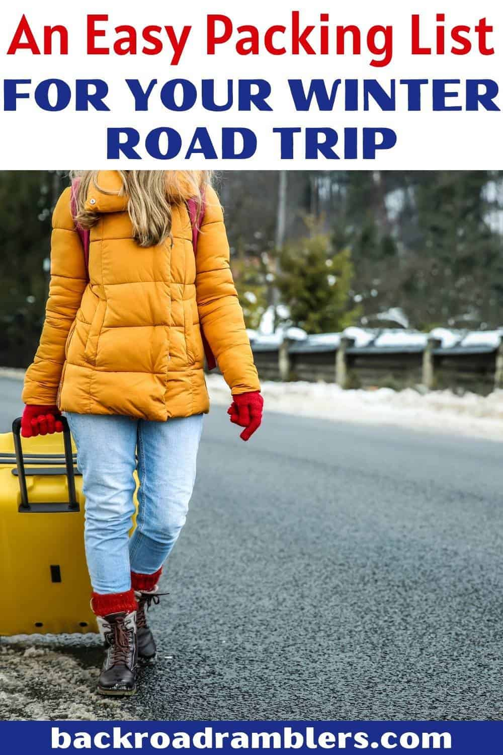 A woman with a yellow jacket pulls a yellow suitcase down the road in the winter. Text overlay: An easy packing list for your winter road trip.